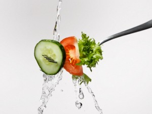 Fresh salad on fork splashed with water