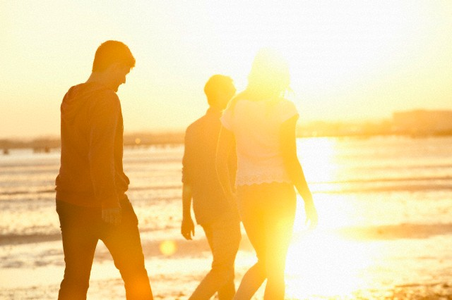 Friends walking on beach at sunset