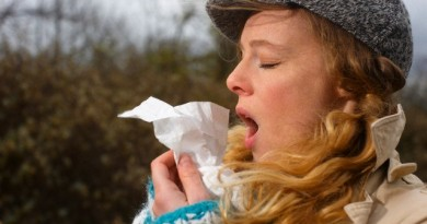 A woman sneezing into a tissue --- Image by © Altrendo/Juice Images/Corbis